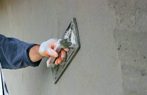 Man's hand plastering a wall with trowel. Selective focus.